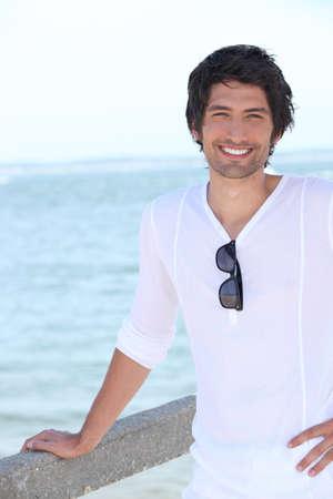 dark haired: handsome guy posing against sea background