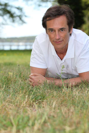 Man lying in the grass photo