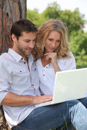 35 39 years: couple leaning on tree with laptop