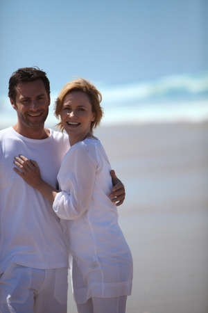 35 39 years: Mature couple in white strolling along a sandy beach Stock Photo