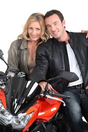 blonde yeux bleus: Chic et Biker avec les bras autour de motard Banque d'images