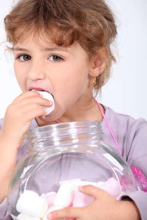 Girl eating marshmallows Stock Photo - 12907919