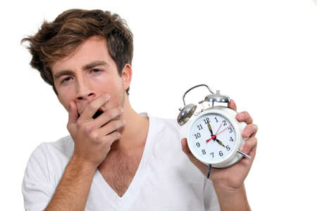 Yawning man holding alarm clock photo
