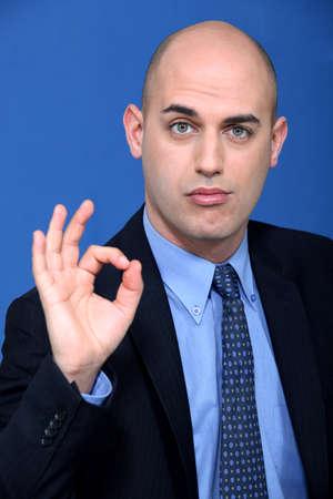 adequate: Bald businessman making ok gesture Stock Photo