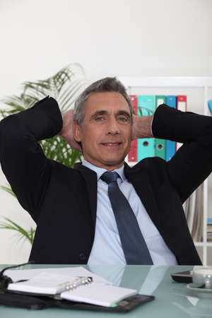 Portrait of an arrogant businessman with his hands behind his head photo