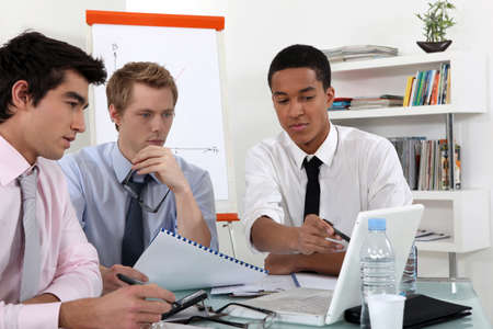 conferring: Young business professional discussing the results of a report Stock Photo