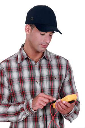 young electrician wearing cap using tester Stock Photo - 12763411