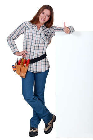 concurrence: Handywoman standing next to a blank sign and giving the thumb