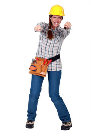 squinting: Tradeswoman gripping an invisible object and squinting Stock Photo