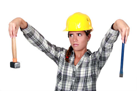apprehensive: Apprehensive tradeswoman holding a hammer and chisel Stock Photo