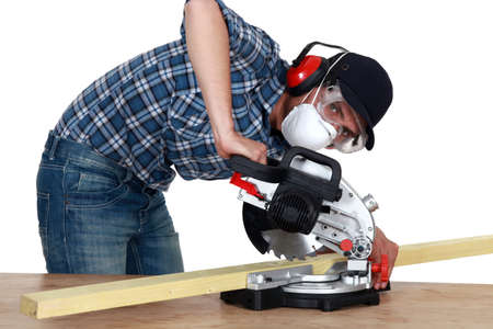 exaggerate: Man using a mitre saw