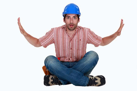 hard bound: Astonished tradesman pushing against invisible walls Stock Photo