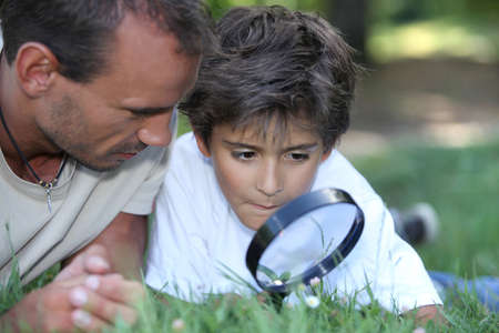 father and kid with magnifying glass photo