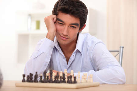 Young man playing chess photo