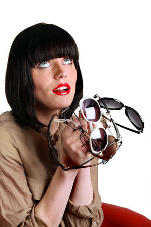 bulging eyes: Woman holding several pairs of sunglasses