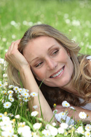 35 39 years: Closeup of smiling woman amongst the daisies