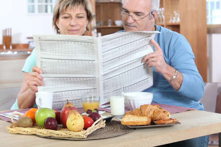 Couple reading newspaper at breakfast photo