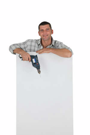 Man with drill leaning on a white sign photo