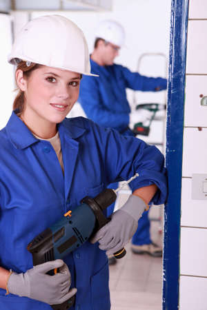 Young female electrician with a power drill Stock Photo - 12729121