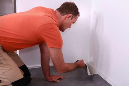 refurbishing: Workman putting down linoleum flooring
