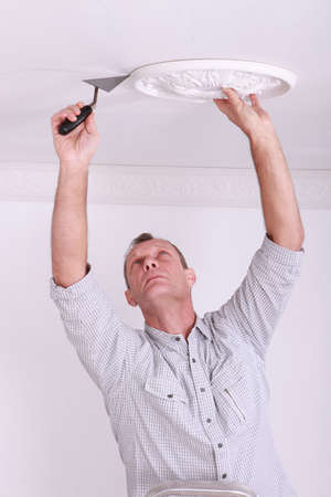 Man fitting a ceiling rose photo