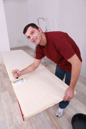 Man painting wooden plank photo