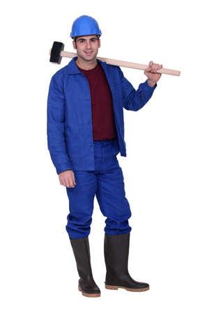 sledge hammer: Man casually stood with sledge-hammer resting on shoulder