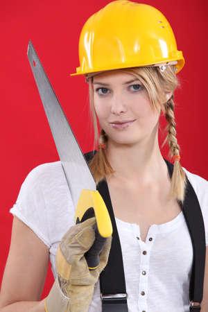 serrucho: Mujer con un casco de seguridad y la sierra de mano Foto de archivo