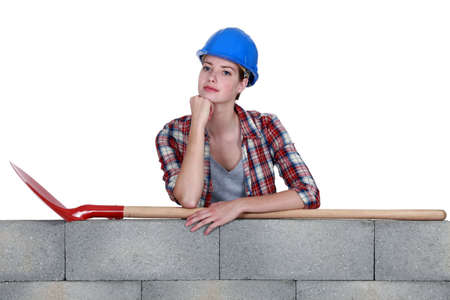 leveler: Woman with spade stood by wall Stock Photo