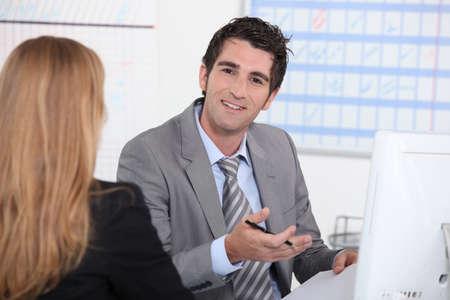 Uomo che lavora al computer con un cliente