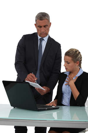 taking notes: Boss handing note to young assistant