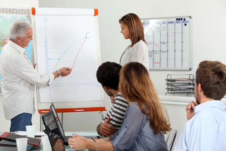 conclusions: Employees looking a line chart Stock Photo