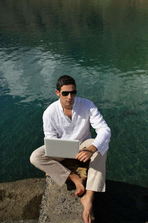 artificial model: Man using his laptop by the water Stock Photo