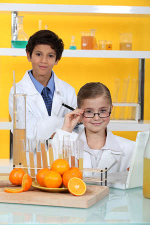 pungency: Children doing chemistry experiments with orange juice