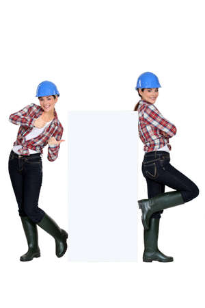 ebullient: Twins standing around a blank sign Stock Photo