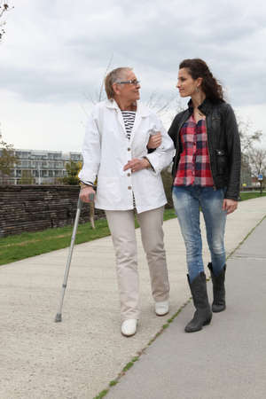 crutch: young woman assisting a senior lady