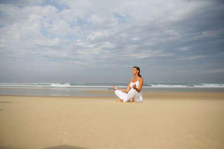 woman meditating on the beach photo