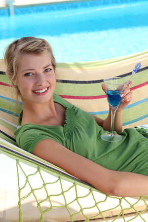 a woman drinking a cocktail near a swimming-pool photo