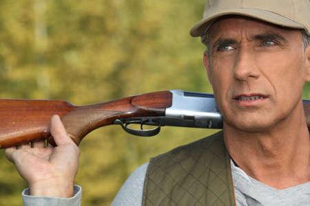 hombre disparando: Hunter sostiene su escopeta sobre sus hombros