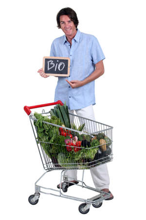 organic peppers sign: Man with a shopping trolley of organic produce Stock Photo