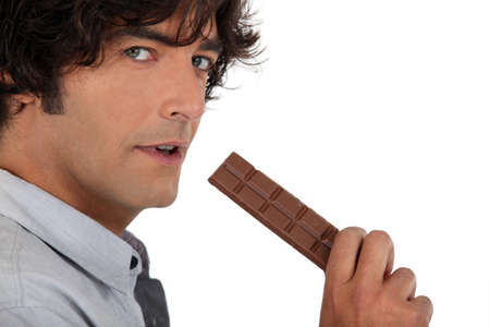 35 years old man eating a chocolate bar photo