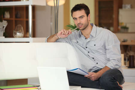look pleased: young man working on his laptop