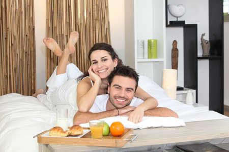 Couple enjoying breakfast in bed photo