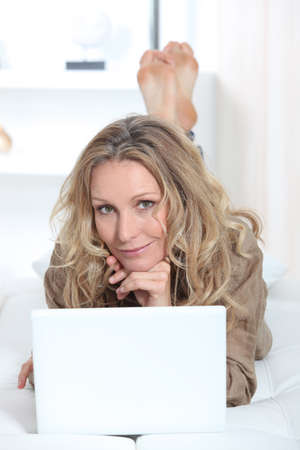 dreaminess: blonde woman doing computer on a couch Stock Photo