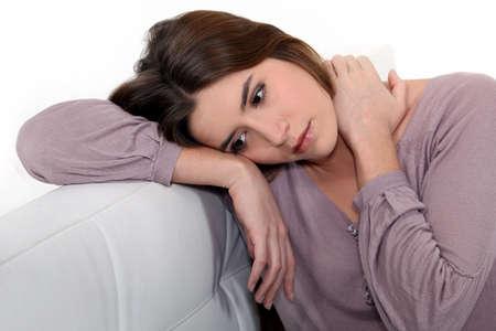 heartsick: Sad woman sitting on a sofa Stock Photo