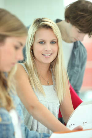 coursework: Pretty female student studying with her friends and their workbooks