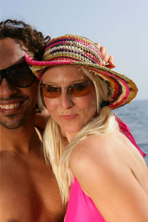 Couple wearing sunglasses at the beach photo