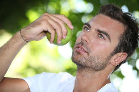 beau jeune homme: L'homme qui mange une pomme sous un arbre
