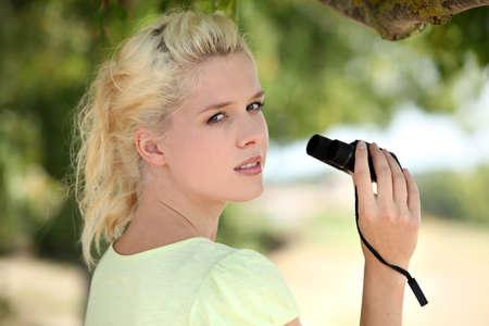 Woman using pair of binoculars photo