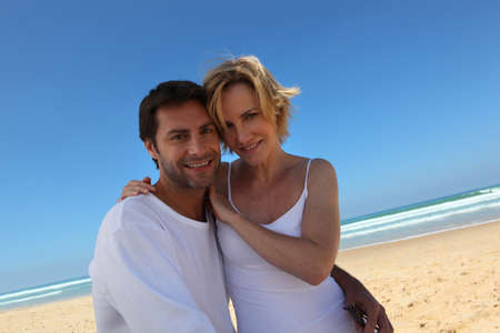 35 39 years: Loving couple wearing white enjoying the beach on a blue sky day